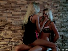 Andrea Francis and Clara G. play with a strap on indoors