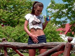 Skinny slut Rikki pounds her vag with a dildo in the yard