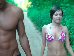 Black dude and salty babe walks down the street in bikini and trunks
