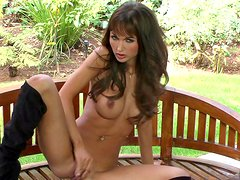 Brunette in boots poses outdoors