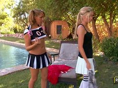Two sexy blonde cheerleaders have lesbian sex by the pool