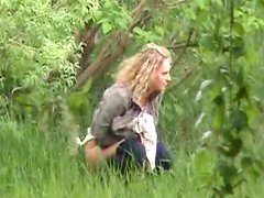 Blond with slender body is pissing outdoors