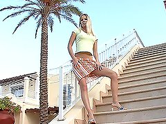 Naughty blonde girl pleases herself on the stairs