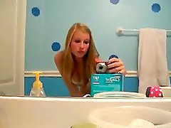 Cute brown-haired girl dancing temptingly in the bathroom