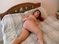 Big-tittied chick masturbating her hairy pussy in bed