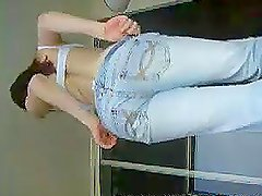 Hot brunette shows a sexy way to take one's jeans off