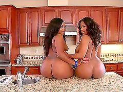 Two ebony girls having interracial threesome sex in the kitchen