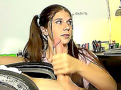 Pretty teen with pigtails gives a handjob and watches TV