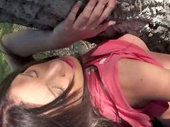 Brunette whore Amy Brooke gives a blowjob hiding from public behind the tree