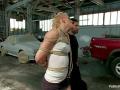 Tied up blondie gets fucked in a car service in public