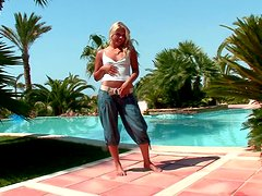 Tanned Rikki fingers her ass and pussy by the pool