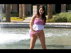 Racquel fingers her pussy behind the public fountain