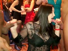 Rapacious brunette in sexy dress sucks a tasty lollicock through the glory hole
