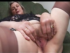 Busty granny shows off hairy pussy