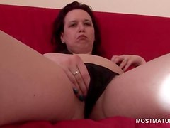 Mature brunette playing with her hungry pussy on the sofa