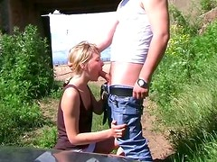 Slutty blond milf gives a head to horny dude outdoors