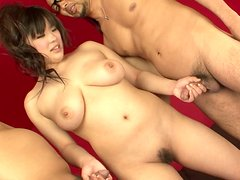 Perverted hot brunette from Asia is fond of giving a titfuck to two dudes