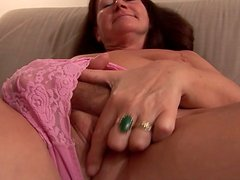 Dirty granny Ome Gusti masturbates on a couch fingering her snatch