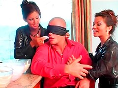 Blindfolded man and ladies in shiny blouses