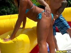 Wet Summer Foursome Outdoors in an Inflatable Slide with Two Latinas