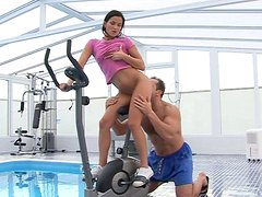 Sporty brunette switches from training to giving a stout blowjob by the pool