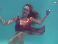 Young redhead swims in a pretty dress