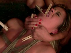Sophisticated domina pins clothing pegs to tongue and tits of salty blondie