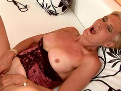Classy looking granny wearing corset is getting toy fucked on cam