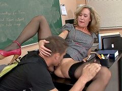Whorish blond teacher pleases her student with a skillful blowjob