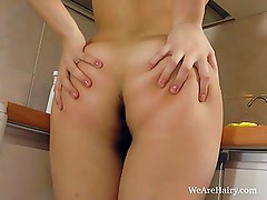 Dana plays with her hairy pussy on the counter