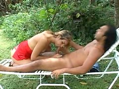 Blonde whore wearing a red dress has anal on the deck chair