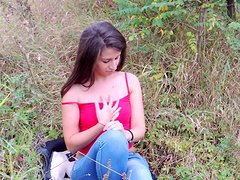 Spicy brunette takes off her jeans outdoors