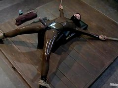 Submissive girl in latex bodysuit gets punished by a girl