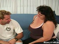 Busty dark-haired mom Jenny gives a blowjob and a titjob to some guy