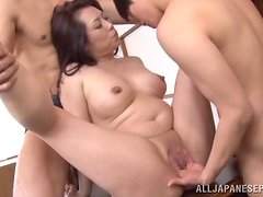 Japanese cougar Neko Ayami gets fucked by two studs in the kitchen