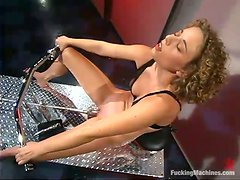 Awesome curly-haired girl plays with a fucking machine in a bar