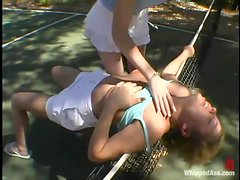 A girl gets tortured and fucked by her GF on a tennis court