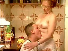 A strong dude is banging that weak granny in the kitchen
