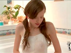 Petite pigtailed girl takes a bath
