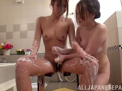 Two Japanese babes share a hard cock in a bathroom