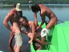 Cute Russian girl is pleasing three horny studs on a boat under the open sky