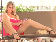 A charming blonde in a pink dress fingers herself outdoors