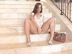 A hot girl toys her pussy with a pink dildo sitting on the steps