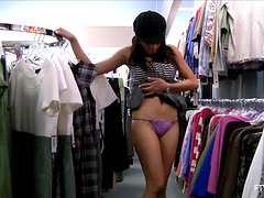 A playful girl shows her nice booty in a clothing store