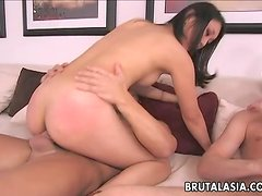 A slim Asian babe gets butt fucked in threesome video