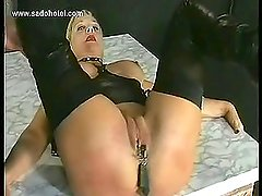 Scared looking milf slave with nice tits gets her pussy spread and metal clamps on pussylips