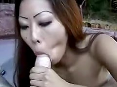 Asian whore with ugly face is sucking schlong outdoors