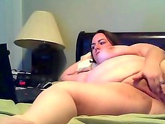 fat milf with big tits laying on the bed rubbing her fat pussy