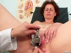 Mature in glasses takes speculum in pussy