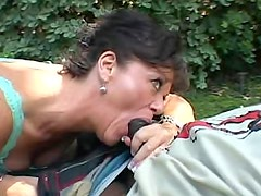 Mature on her knees sucking black cock